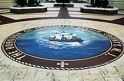 "Concrete overlay circle logo of a ship on the blue ocean states ""the borough of Edgewater Hergen County NJ"" has a stamped patterned concrete around the smooth logo area."