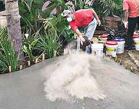 throwing color hardener onto a slab of concrete where proper safety equipment