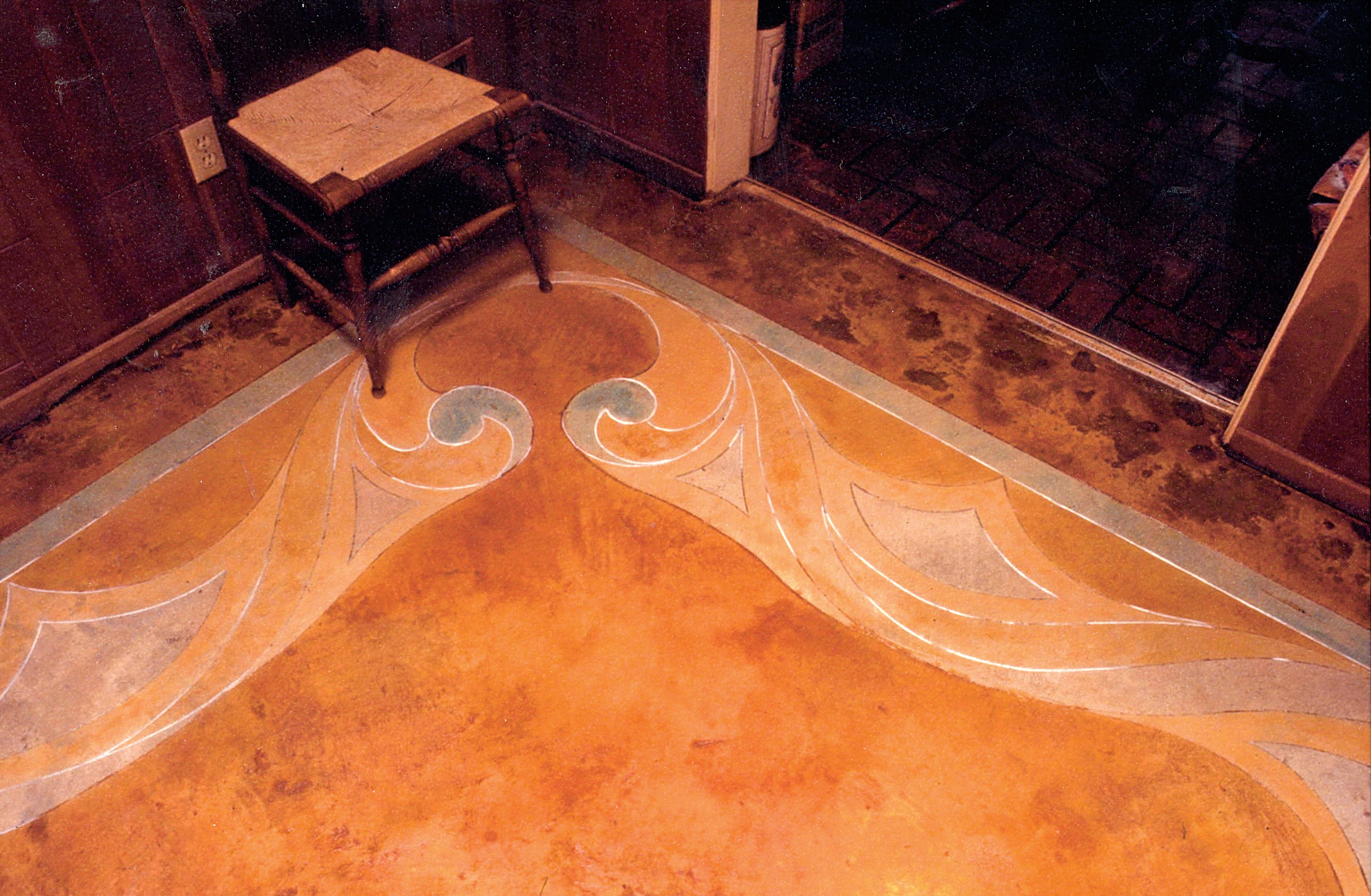 In this living room the concrete was cleared of tack strips and glue and then thoroughly cleaned. The lines and flowing curves were drawn freehand using green chalk.