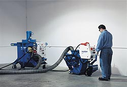 Shot blasting equipment in use on a concrete floor.