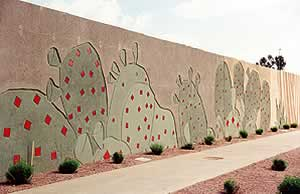 Concrete wall with imprinted cacti with red dots created by using concrete form liners and detailing with concrete stain. Decorative walls by Scott System.
