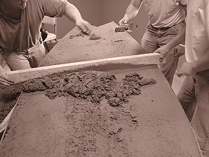 Making a concrete tabletop in the shape of a surfboard starts with smoothing the top of the form with a straight edge.
