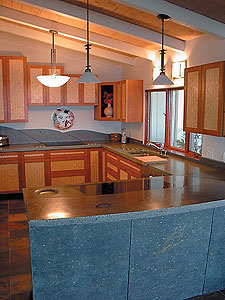 Lokahi Stone - full kitchen concrete countertop with a waterfall edge in grayish green color.