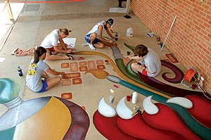 Students Apply Color to a public art project on a concrete sidewalk.