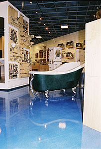 Soy-based Concrete Stains in a show room with a claw foot bath tub sitting center. The stained floor is an ocean blue that was achieved by many thin coats of concrete stain instead of one thick coat.