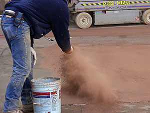 Throwing concrete release agents onto a ready to stamp concrete slab.
