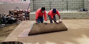 Placing concrete stamping skins onto a concrete slab that has concrete release powder on the slab.