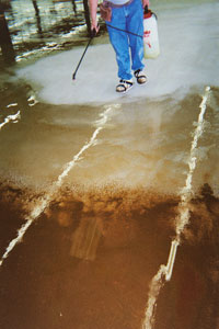 Applying Concrete Sealer with a conventional pump sprayer onto a two tone brown acid stained concrete floor.