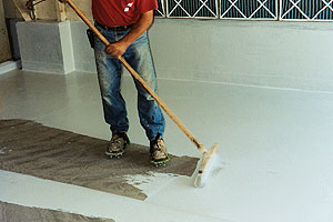 Applying Concrete Sealer to a concrete floor with a squeegee.
