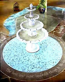 Acanthus Concrete Stain Designs fountain stands on a bright blue and brown stained concrete circle.