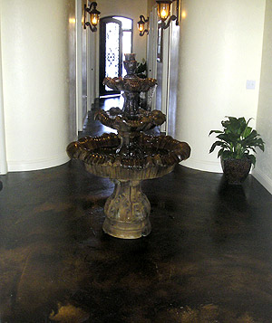 Concrete fountain placed on a brown stained concrete floor.