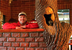Kevin Winkler next to his faux tree that was carved and stained to look like an animal was peering out.