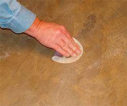 As the material cures, the repair is blended into the surrounding concrete with sandpaper.