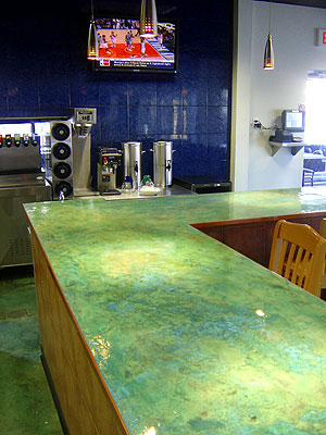 Matt Hine applied a white-based microtopping in layers to produce a texture variance on this commercial bar top. He applied a turquoise acid stain over these layers to achieve a multitoned effect, finishing off the job with an epoxy topcoat.