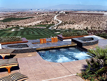 Concrete pool deck and water features overlooking a golf course below.