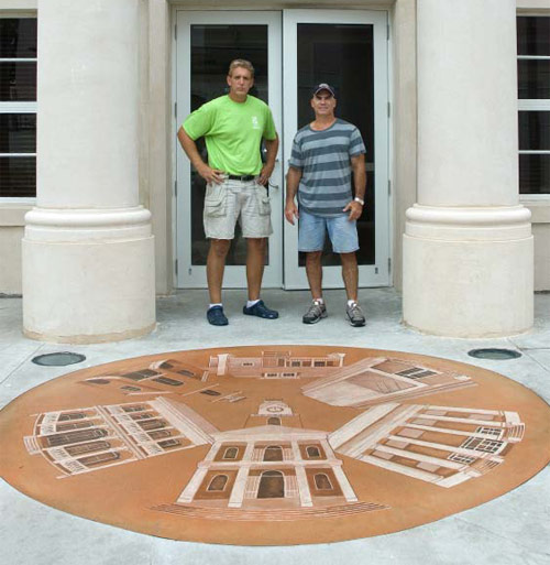 Steven Ochs and Gerald Taylor stand behind their mural at the Freeman Justice Center in Key West, Florida.