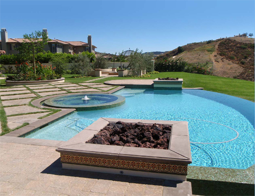 Pool Deck Ideas with clean clear water and a firepit and a fountain.