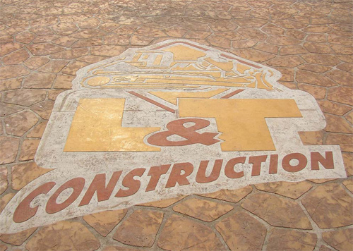 Concrete Stenci of L & T construction's logo in the driveway of this business.